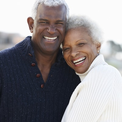 Old couple laughing and having fun after their restorative dentistry visit, which included getting new dentures