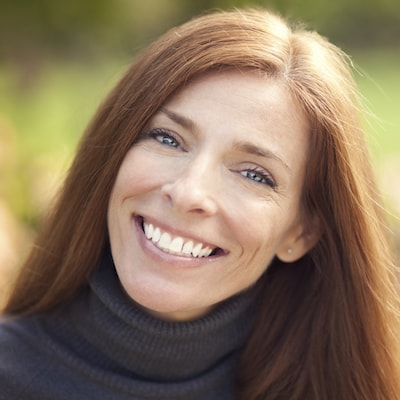 Middle-aged lady smiling outside because she had her gums contoured as part of restorative dentistry in Baton Rouge