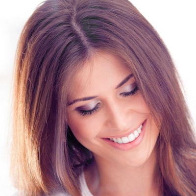 Woman looking down but smiling as she uses Clear Correct as part of her restorative dentistry treatment plan