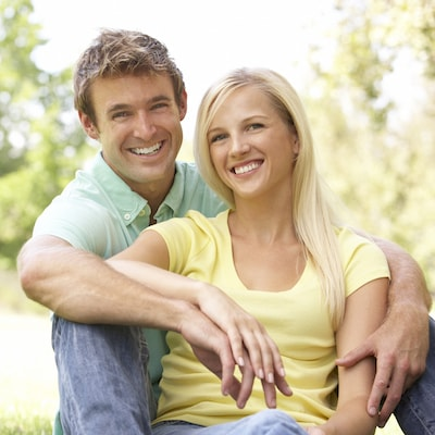 Young couple smiling outside because they enjoyed Baton Rouge restorative dentistry and their root canal care