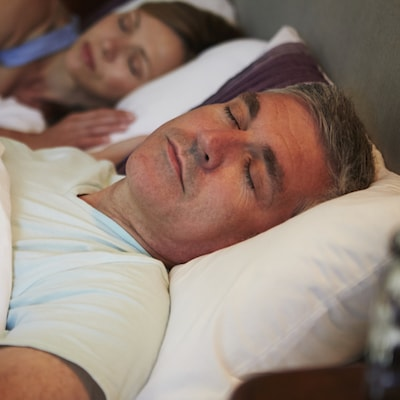 Man sleeping next to his wife thanks to a successful restorative dentistry visit for sleep apnea