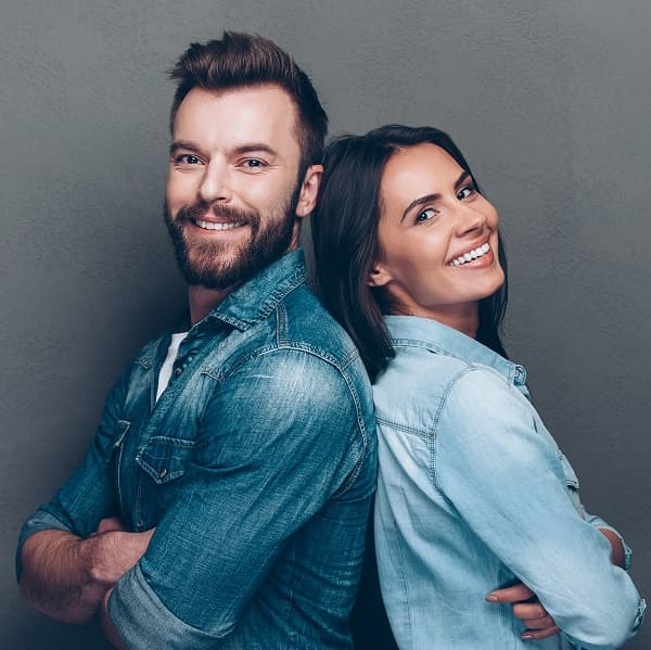 Smiling man and woman with bright, white teeth because of teeth whitening treatment.