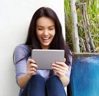 Smiling woman holding and looking at a tablet.