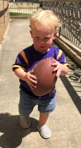 Little blonde-haired boy with a football.